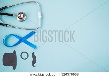 Light blue ribbons with black mustache, top hat and stethoscope on blue background, prostate cancer awareness,  Men health awareness, November blue. copy space. stock photo