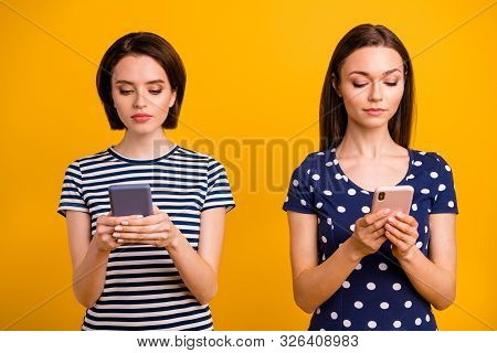 Photo of two pretty ladies holding telephones addicted to instagram followers and comments wear summer casual trendy t-shirts isolated yellow background stock photo