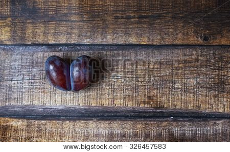 Ugly plum. A spoiled purple heart-shaped plum on a brown wooden background. Ugly fruit. Funny food. Spoiled food. stock photo