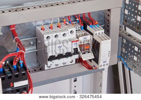 Circuit breakers, intermediate relay and phase control relay in the electrical Cabinet. Wires are connected to the electrical equipment according to the scheme. Automation of electrical equipment. stock photo
