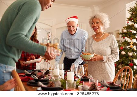 Multi-Generation Family In Dining Room Putting Christmas Meal On Decorated Table stock photo