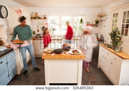 Motion Blur Shot Of Family In Kitchen Helping To Prepare Christmas Meal Together stock photo