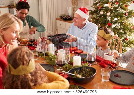 Multi-Generation Family Sitting At Dining Table Enjoying Christmas Meal At Home Together stock photo