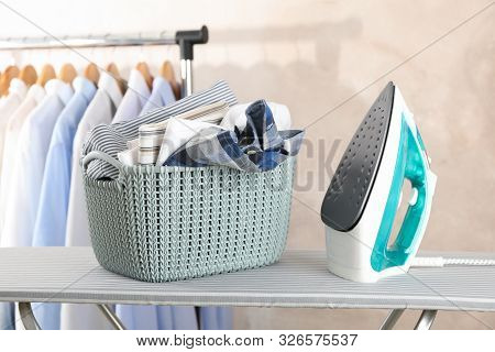 Basket with clean laundry and iron on ironing board, space for text stock photo