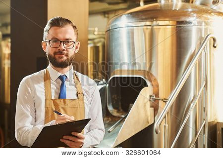 Adult expert monitoring brewery pocess and writing. Handsome, bearded man in glasses, white shirt, tie and brown apron holding folder and pen, posing, looking at camera. stock photo