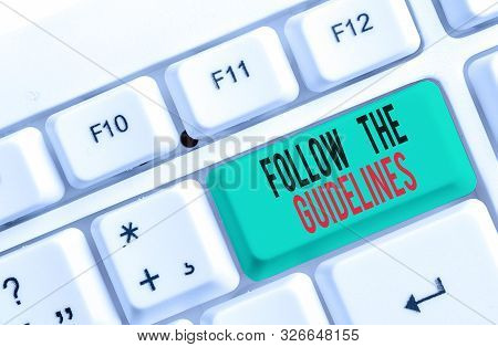 Text sign showing Follow The Guidelines. Conceptual photo Manual of Style Follow a Specified Rule Accordingly White pc keyboard with empty note paper above white background key copy space. stock photo