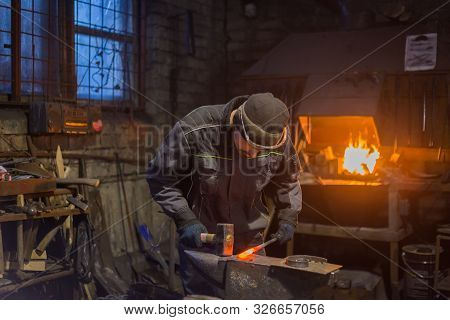 Professional blacksmith forging molten metal on anvil at smithy, workshop. Handmade, craftsmanship and blacksmithing concept stock photo