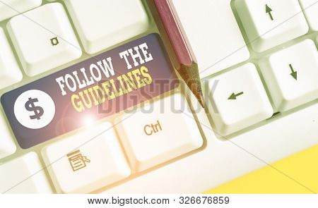 Word writing text Follow The Guidelines. Business concept for Manual of Style Follow a Specified Rule Accordingly White pc keyboard with empty note paper above white background key copy space. stock photo