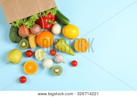 Paper bag, vegetables and fruits on blue background, space for text stock photo