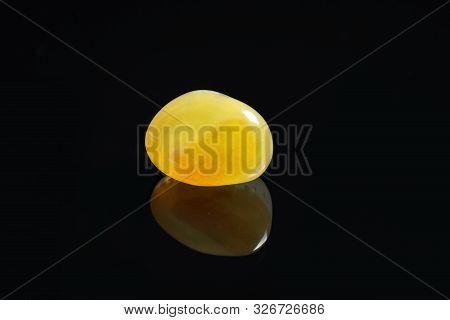 Beautiful honey agate gemstone on black background stock photo