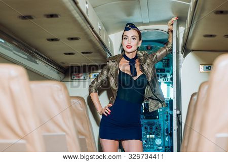Traveling and jet plane flying. Flight attendant uniform. Stewardess and travel time. Attendant and airhostess. Portrait of smiling flight attendant serving in airplane stock photo