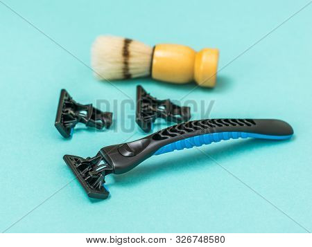 Black razor with two replacement blades and a shaving brush for shaving on a blue background. Set for care of a mans face. stock photo