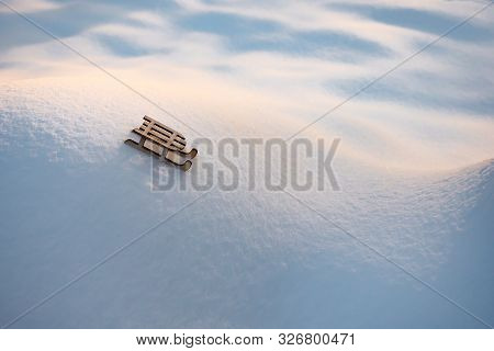 Toy on white snow. Sleigh on snowy hills and valleys. Toy of wooden sleigh on snow background. Greeting card for winter holiday. Symbol of new year. Greeting card, brochure. Background of snow stock photo