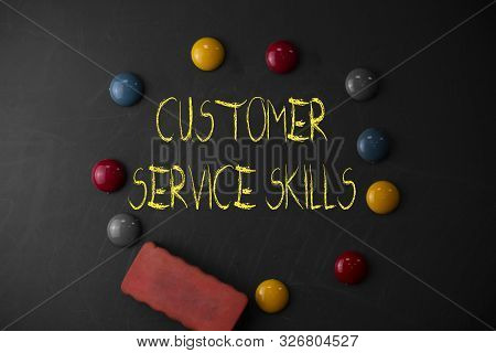 Word writing text Customer Service Skills. Business concept for Aptitude to master to improve dealings with client Round Flat shape stones with one eraser stick to old chalk black board. stock photo
