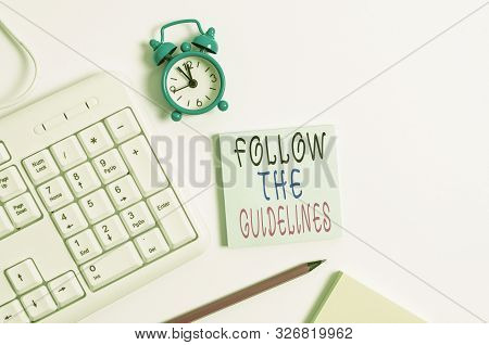 Conceptual hand writing showing Follow The Guidelines. Business photo showcasing Manual of Style Follow a Specified Rule Accordingly Keyboard with empty note paper and pencil white background. stock photo