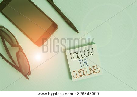 Handwriting text writing Follow The Guidelines. Concept meaning Manual of Style Follow a Specified Rule Accordingly Eyeglasses colored sticky note smartphone cell pen cool pastel background. stock photo