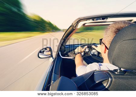 Man driving a convertible car on country road. View from the inside behind the driver. man is driving at high speed on the highway. Dangerous fast driving. Motion blur effect stock photo