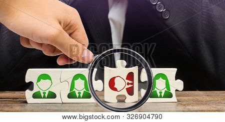A magnifying glass looks at a businessman sitting in despair over the not assembled puzzles symbolizing a team of employees. Toxic or incompetent worker who fails to comply tasks and disrupts stock photo