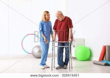 Caretaker helping elderly man with walking frame indoors stock photo