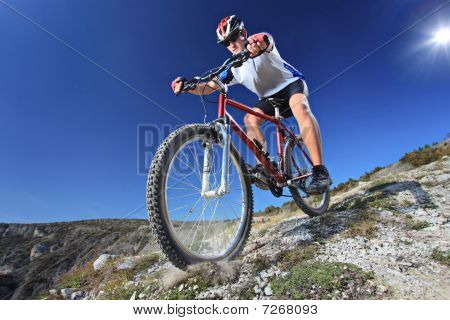 A person riding a bike downhill style stock photo