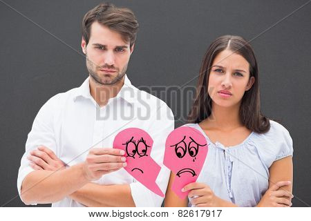 Upset couple holding two halves of broken heart against grey stock photo