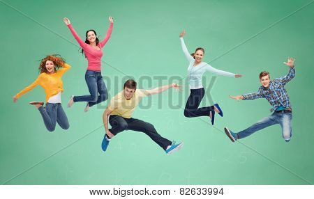 happiness, freedom, friendship, education and people concept - group of smiling teenagers jumping in