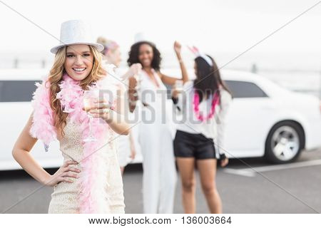 Frivolous women drinking champagne next to a limousine on a night out stock photo
