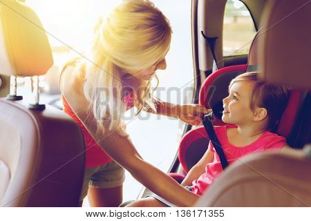 family, transport, safety, road trip and people concept - happy mother fastening child with car seat