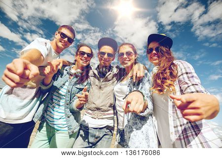 summer holidays and teenage concept - group of smiling teenagers in sunglasses hanging outside point