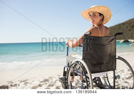 Wheelchair woman sitting smiling at camera on the beach stock photo