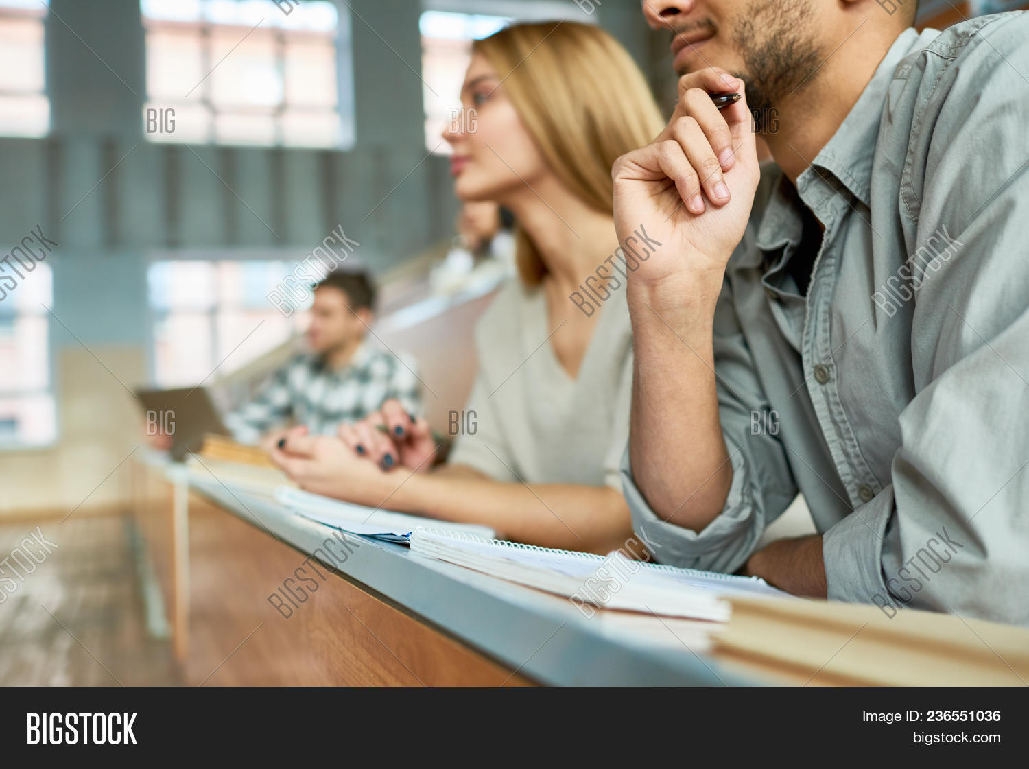Multi-ethnic group of students sitting at desk in lecture hall of modern college and listening to professor, focus on young Middle-Eastern man, copy space
