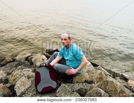 Midle aged man sitting on the shore of the lake. Solitude mature man sitting on the bank. Concept of loneliness. stock photo
