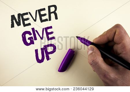 Conceptual hand writing showing Never Give Up. Business photo showcasing Be persistent motivate yourself succeed never look back written by Man plain background holding Marker in Hand. stock photo