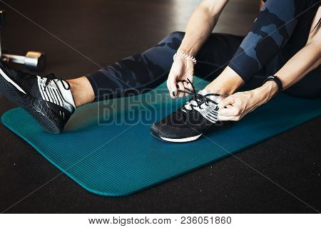 Young attractive brunette girl enlacing her sport shoes after practicing workout training on blue yoga mat. Woman is on foreground and on focus. stock photo