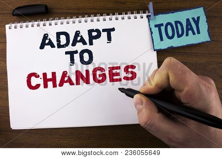Handwriting text writing Adapt To Changes. Concept meaning Innovative changes adaption with technological evolution written by Man Notepad holding Marker wooden background Today Clip. stock photo