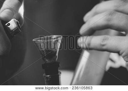Bong lighter for A man smokes cannabis weed, in his hands. Smoke on a black background. Concepts of medical marijuana use and legalization of the cannabis. On a black background stock photo