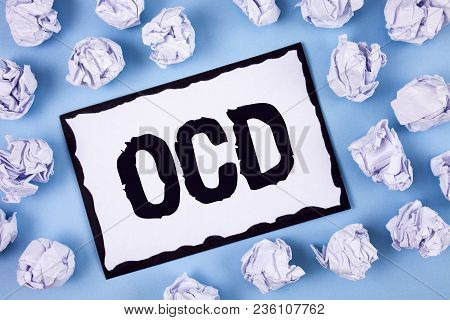 Word writing text Ocd. Business concept for Obsessive Compulsive Disorder Psychological Illness Medical Condition written White Sticky note paper within Paper Balls Plain Blue background. stock photo