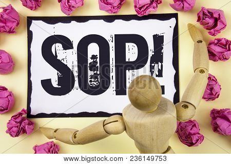 Handwriting text Sop Motivational Call. Concept meaning Standard Operating Procedure Rules Instructions written Sticky Note Paper within Paper Balls plain background Wooden Robot Toy. stock photo