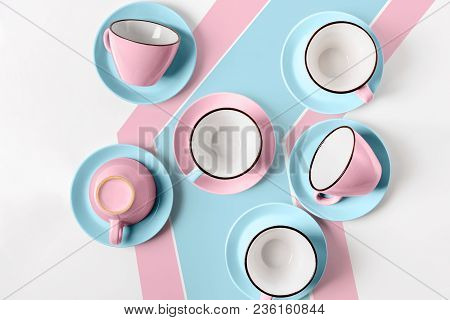 Clean coffee or tea set. Plenty of elegant porcelain light blue and pastel pink cups and at funky abstract background, top view and flat lay. stock photo