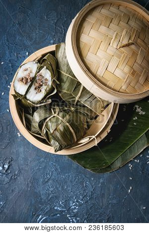 Asian rice piramidal steamed dumplings from rice tapioca flour with meat filling in banana leaves served in bamboo steamer with rice above over blue texture background. Top view, space. stock photo