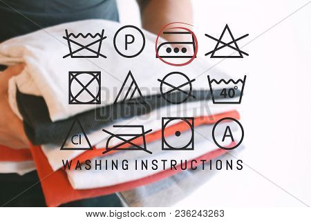 Stack of colorful folded shirts with laundry instructions symbols. Household concept. stock photo