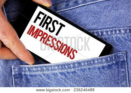 Text sign showing First Impressions. Conceptual photo Encounter presentation performance job interview courtship written Mobile phone holding by man the Blue Jeans background. stock photo