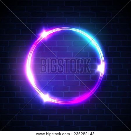 Glowing circle with neon lights on dark brick wall background. 3d neon light advertising tube banner with blank space for text. Night club electric sign. Round bright frame. Color vector illustration. stock photo