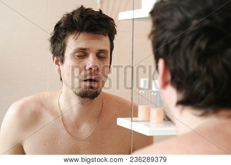 Tired man who has just woken up looks at its reflection in the mirror and sleeping standing still. stock photo
