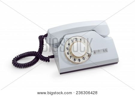 Old desktop telephone set with rotary dial in white plastic housing on a white background stock photo