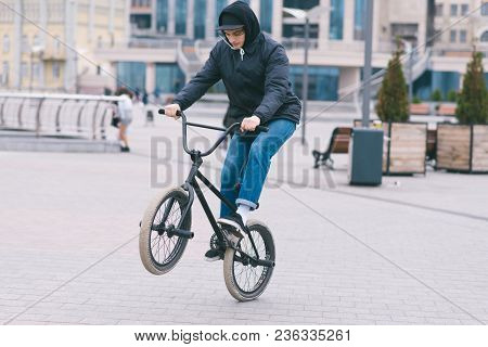 The teen does tricks on the BMX. BMX cyclist rides a bike around the park and makes tricks. BMX concept. stock photo