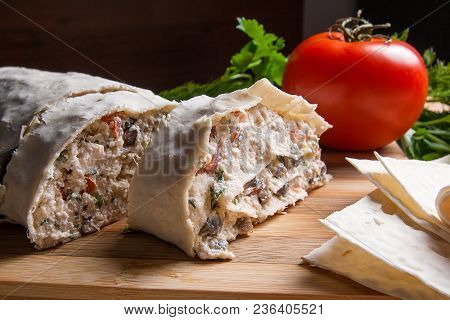 Thin Armenian pita bread or lavash wrapped tomatoes, cottage cheese or curd, chicken meat, tomatoes and herbs - dill, onion, parsley on cutting board. Red ripe tomato and herbs - dill, green onion, parsley. Composition in rustic style on wooden background stock photo