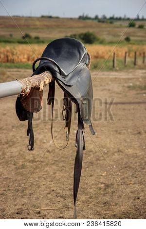 Horse saddle on rural fence. horse saddle close up stock photo