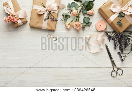 Wedding craft gift boxes on white wooden background. Top view on ribbons, flowers and golden rings, copy space. Memmorable date organization concept stock photo