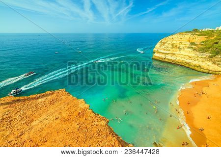 Aerial view of golden cliffs of Praia de Benagil in Algarve near Lagoa, Portugal, Europe. Boat trips to visit the famous landmark Algar de Benagil, the cave near Benagil Beach. Tourism in Algarve. stock photo